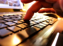 Hands typing on laptop keyboard